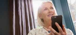 senior woman tracking parkinson's disease symptoms with her mobile phone