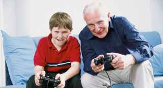 Child playing video game with grandfather