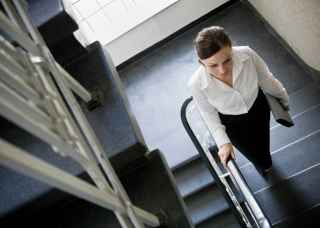 Woman taking the stairs at work for exercise