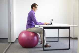 Man sitting on ball at desk