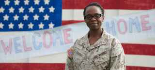 female veteran in front of a welcome home banner and flag