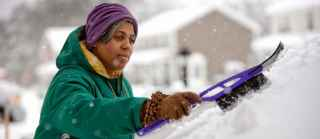 depressed woman scraping windshield in winter
